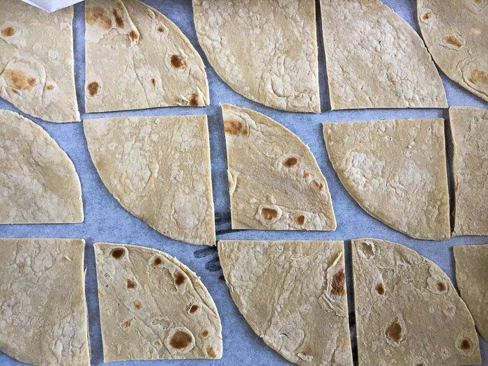 cut tortillas on baking sheet
