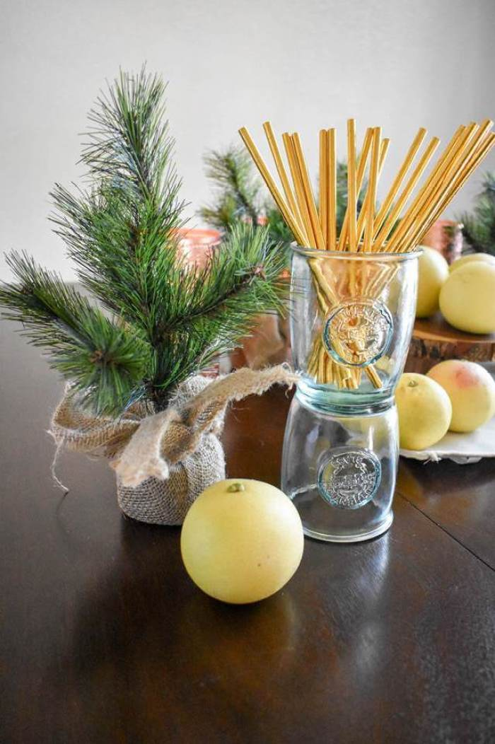 recycled glass cups stacked and filled with gold paper straws next to a faux sapling tree