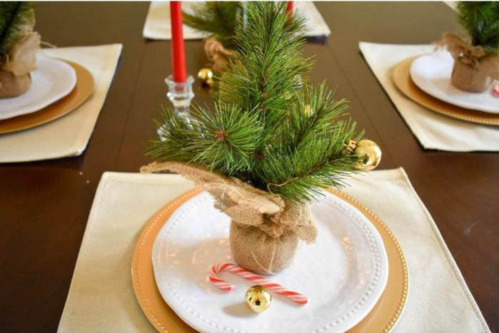 Christmas table place setting with candy cane, mini gold ornament, and faux sapling on plate