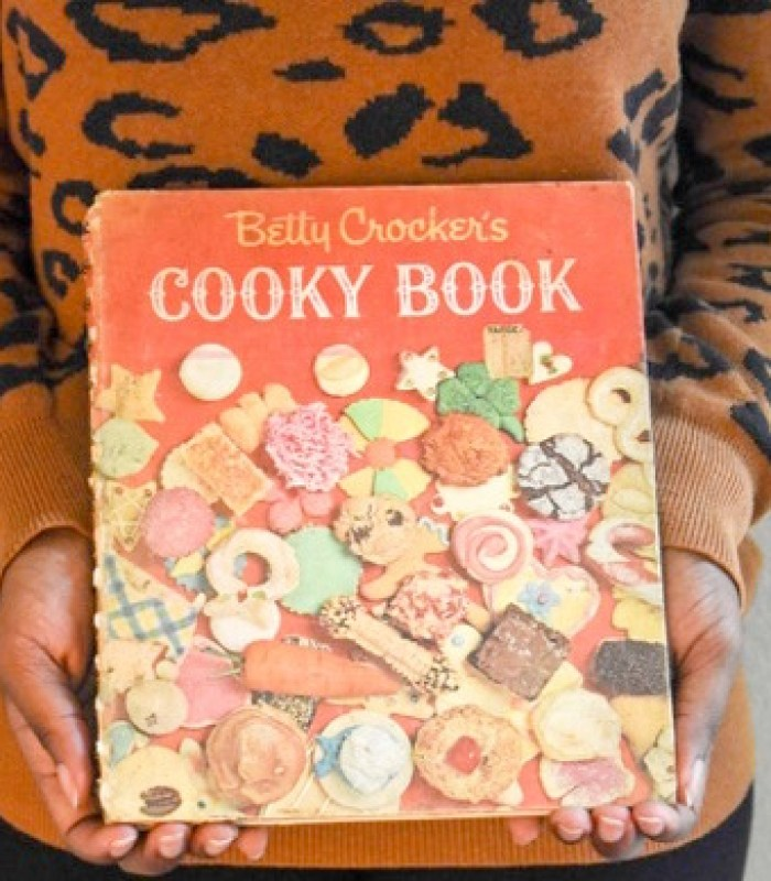holding vintage copy of Betty Crocker's Cooky Book