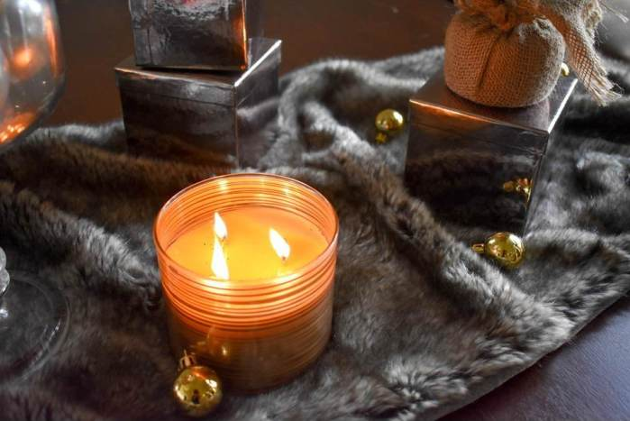 lit three-wick candle on fur table runner