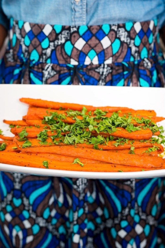 holding dish of roasted carrots garnished with parsley