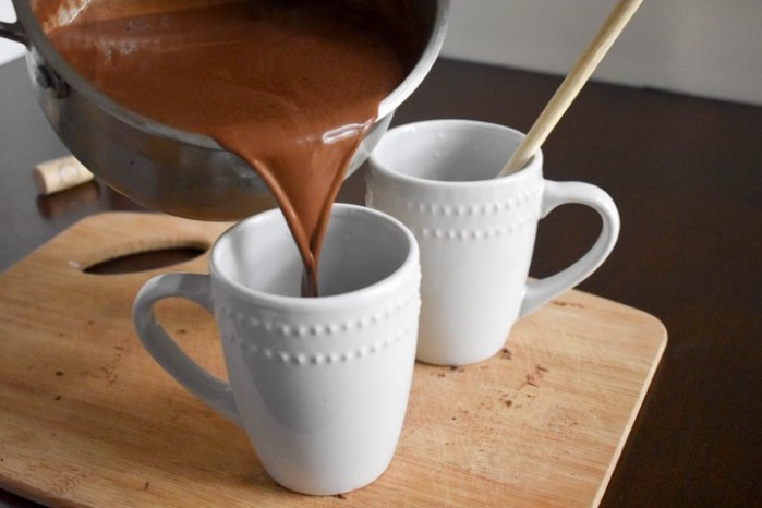 pouring red wine hot chocolate into white mug