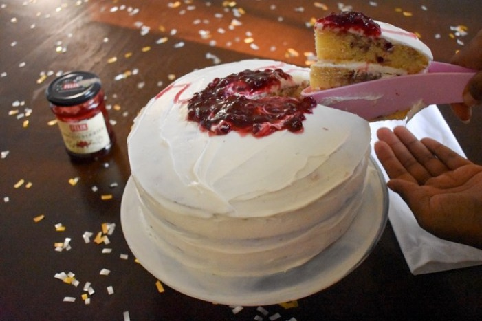cutting and serving berry swirl cake