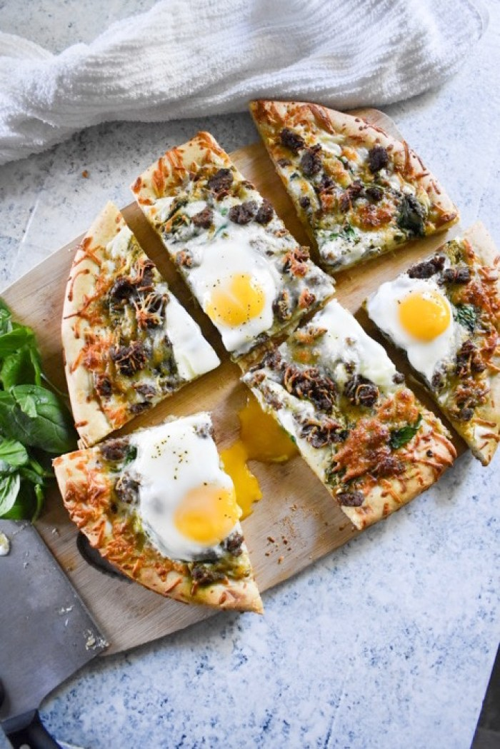 Sliced brunch pizza with runny egg yolk