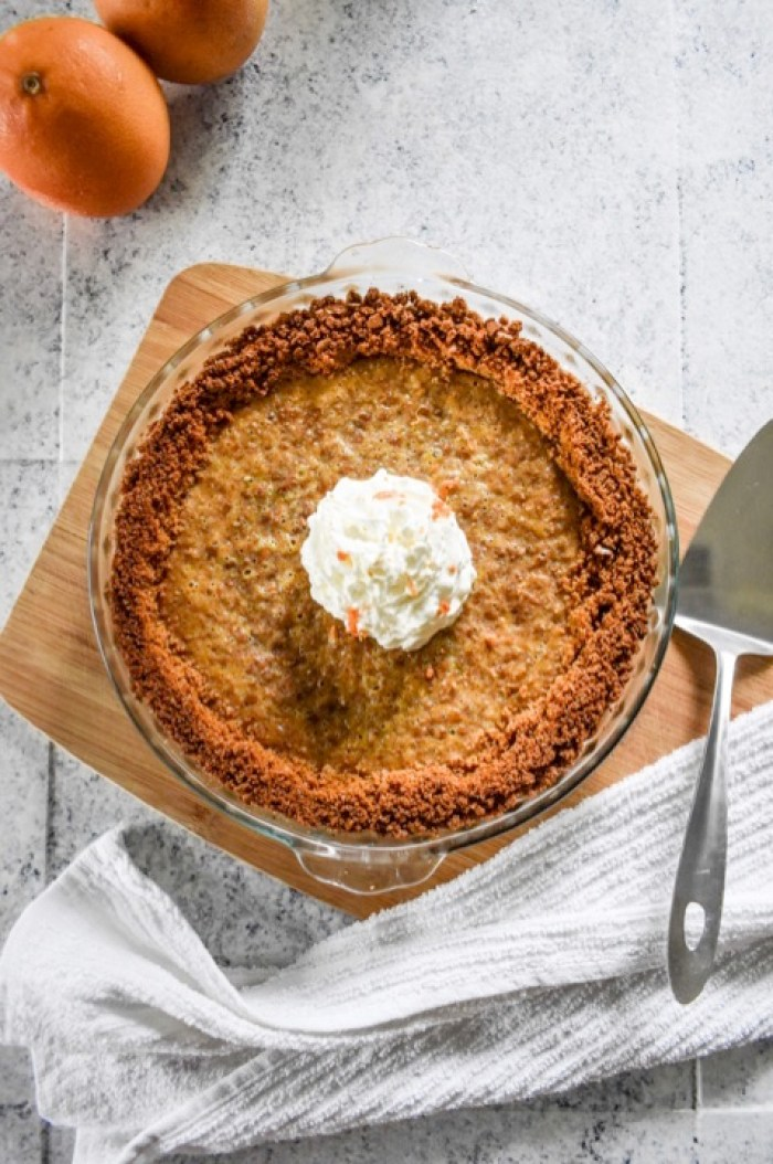 baked grapefruit & ginger pie garnished with whipped cream and grapefruit zest