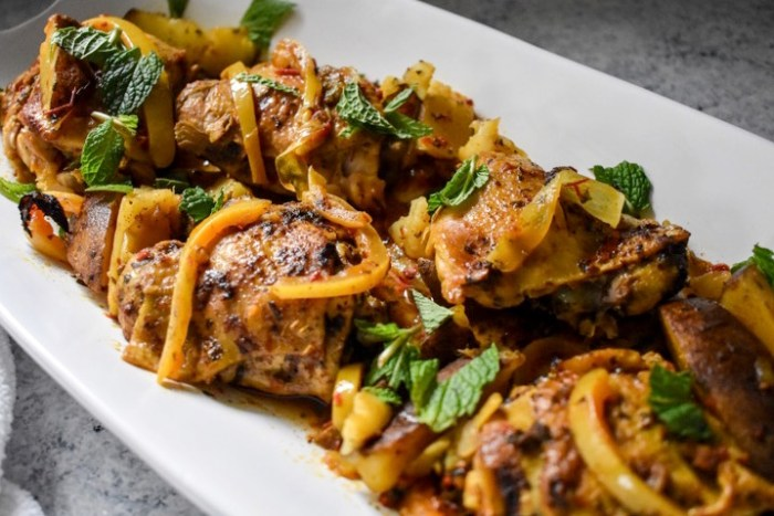slow cooked Moroccan chicken thighs on platter, garnished with preserved lemon and fresh mint.