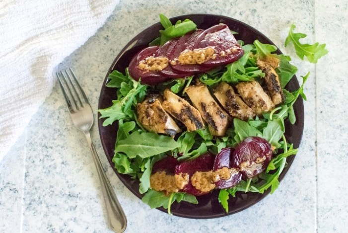marinated grilled chicken and pickled beets on a bed of arugula