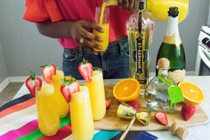 making tequila mimosas with champagne, orange juice, patron, and st germain