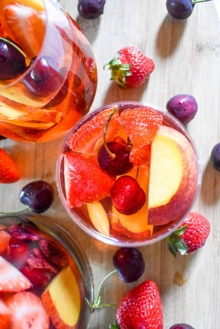 glasses of rosé sangria surrounded by fresh fruit
