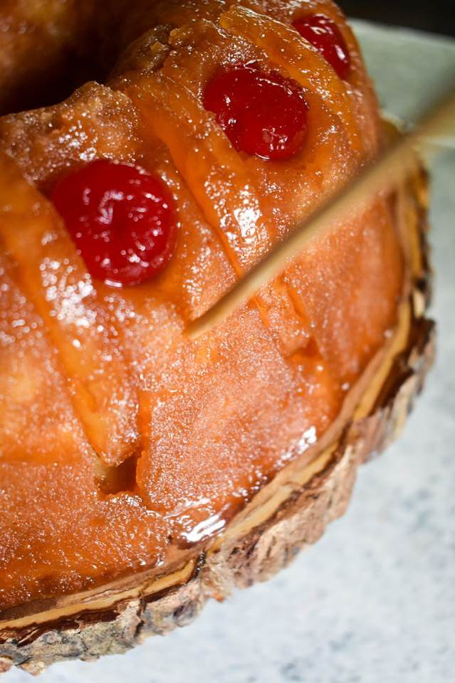 poking holes in pineapple upside down bundt cake with wooden skewer.