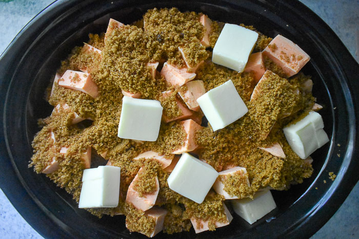 chunks of sweet potato, butter, and brown sugar mixture in slow cooker