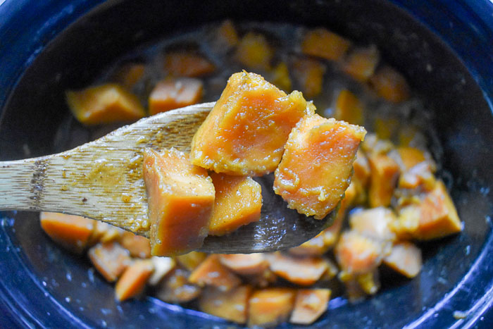 scooping candied sweet potatoes out of slow cooker crock