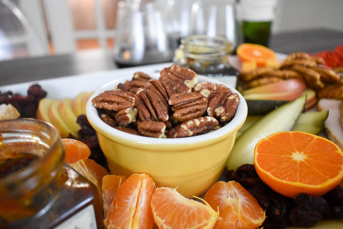 closeup of a small bowl of pecans on a festive thanksgiving appetizer board