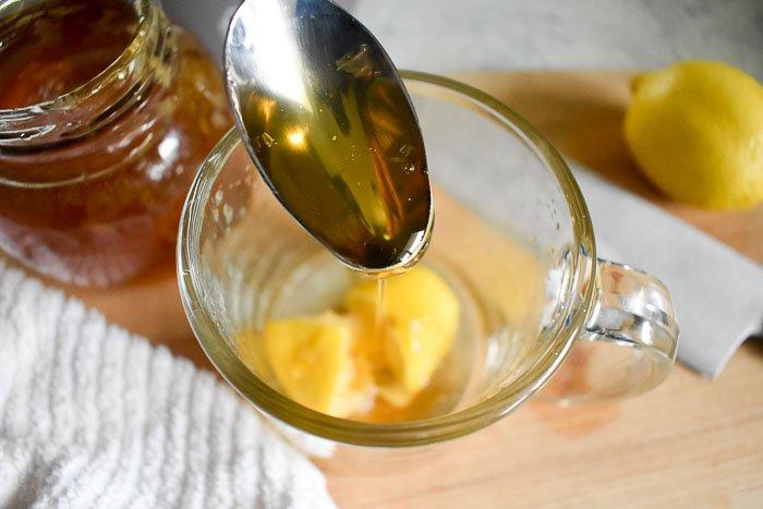 honey being spooned into a mug