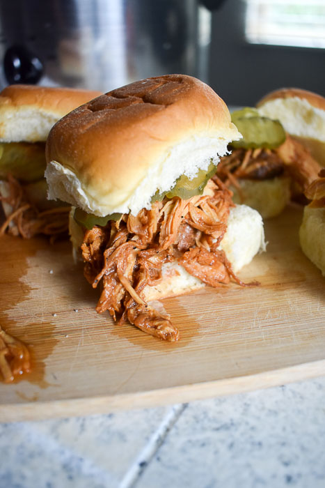 These slow cooker pulled BBQ chicken sliders are as easy as they are tender, juicy, and delicious. Make this set-it-and-forget-it recipe for your next cookout, tailgate, or dinner tonight! Recipe by Dash of Jazz