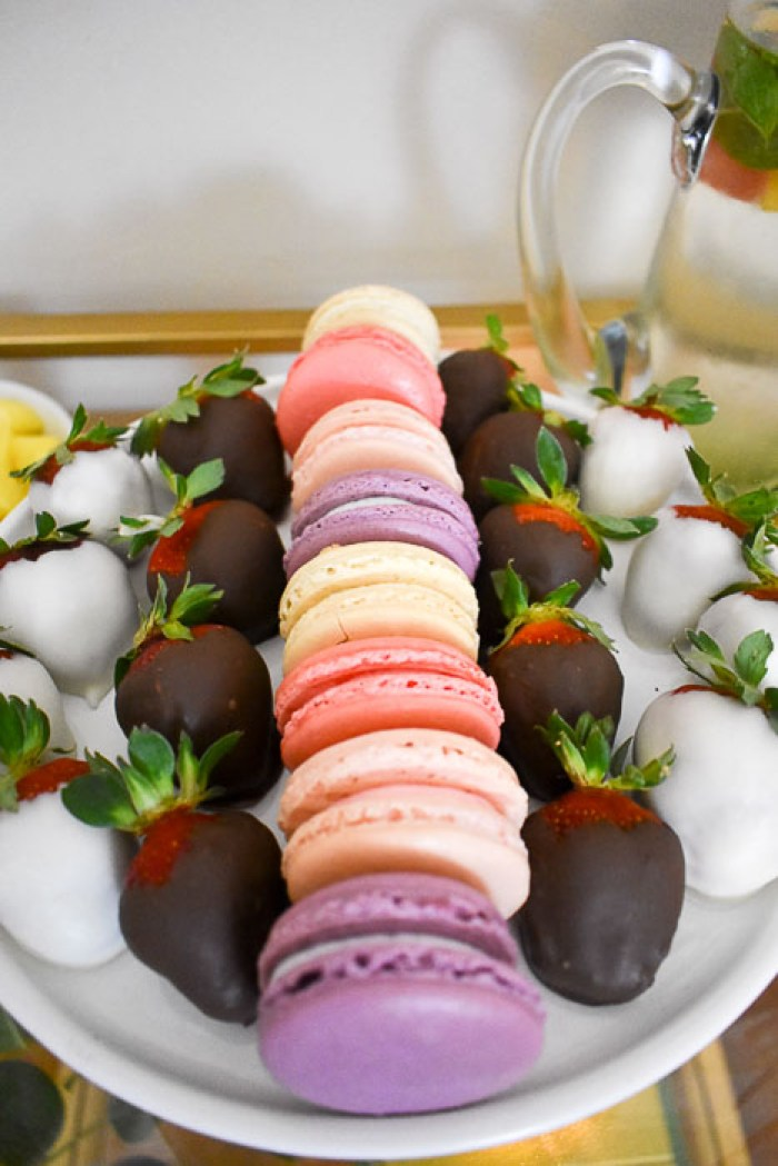 macarons and chocolate covered strawberries on cake stand
