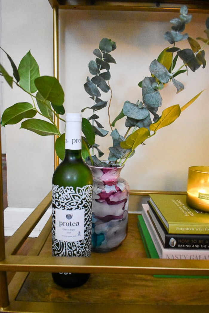 bottle of wine and greenery arrangement in watercolor vase