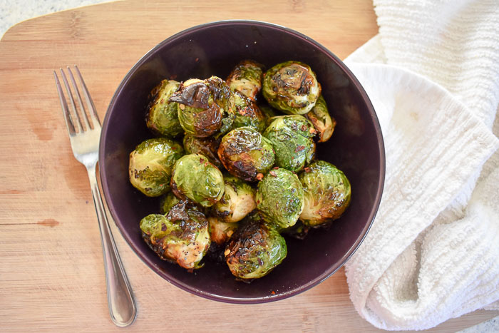 crispy roasted brussels sprouts in a bowl flanked by a fork and white kitchen towel