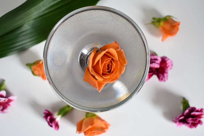 arial view of violet-colored cocktail with orange spray rose floating in it
