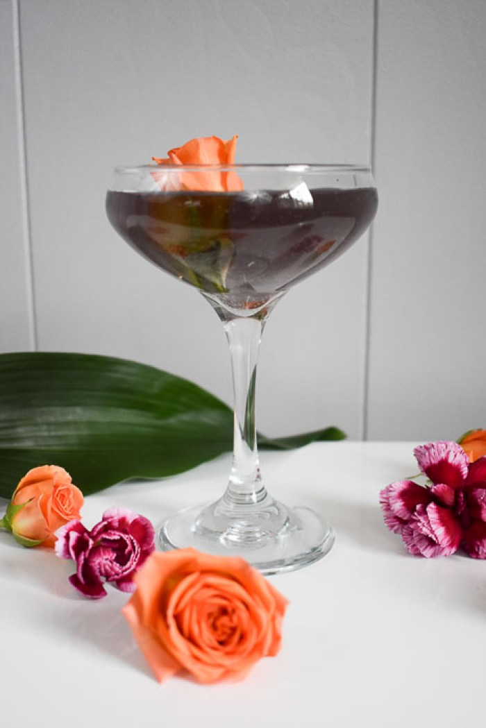 violet gin cocktail with an orange rose garnish