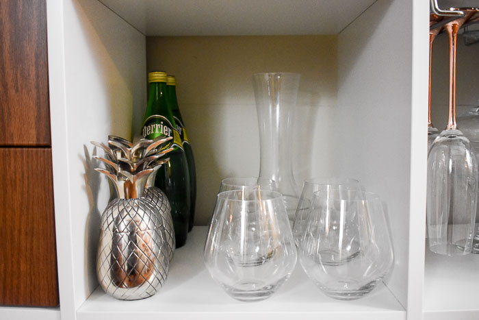 wine and cocktail glasses on a home bar cabinet shelf
