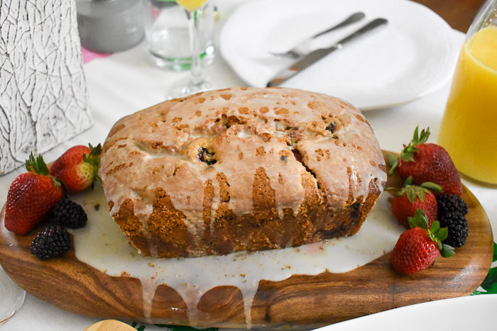 glazed loaf of lemon berry quick bread and fresh berries