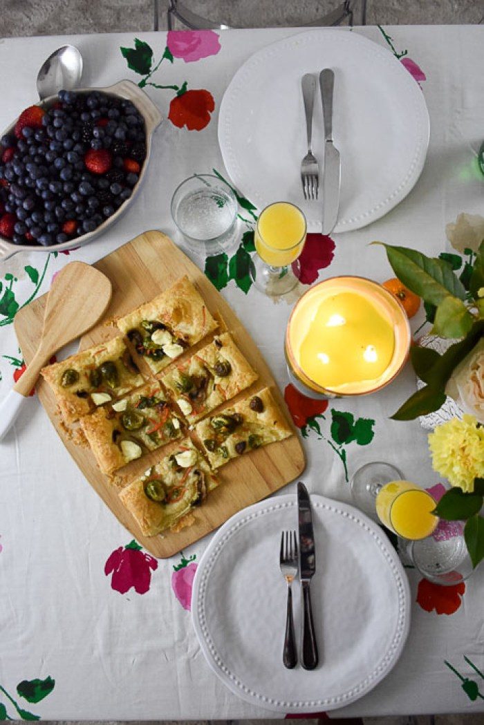 arial view of brunch tablescape including a green candle, fresh berries, and a puff pastry pizza