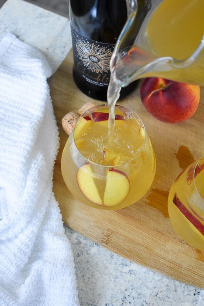 pouring lemon ginger bellini punch into stemless wine goblet