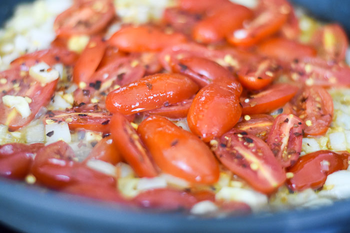 tomatoes, onions, and garlic cooking in pan with crushed red pepper
