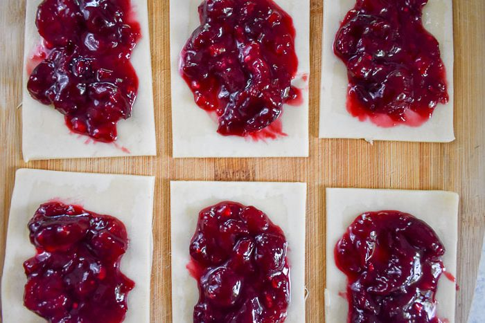 homemade cherry pop tart filling on squares of dough