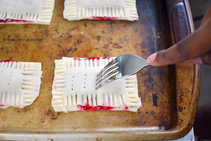 scoring unbaked homemade cherry pop tarts with fork before baking