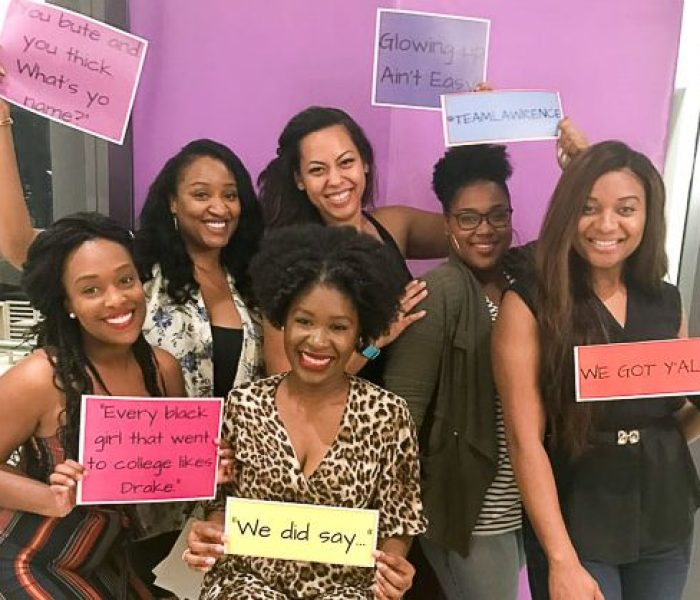 six women holding signs with Insecure HBO show quotes, posing for a picture.