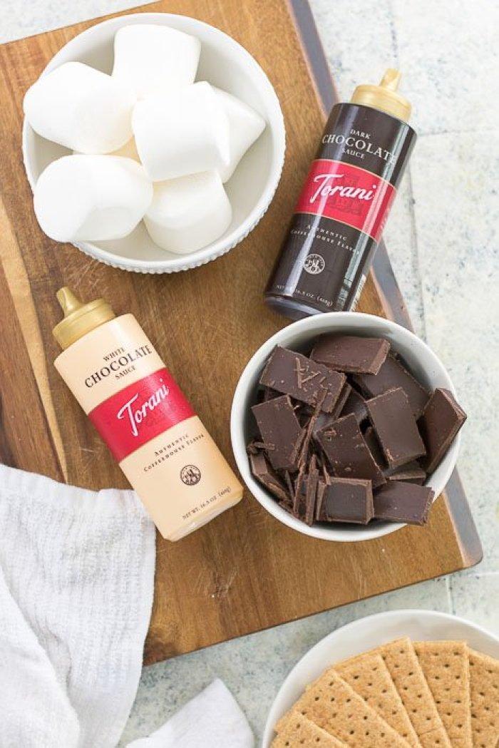 dark chocolate, marshmallows, graham crackers, and Torani sauces laid on countertop