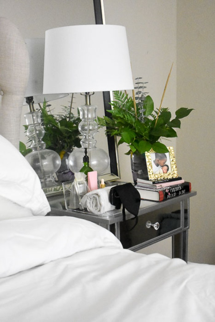 nightstand table stocked with items for guests and fresh greenery
