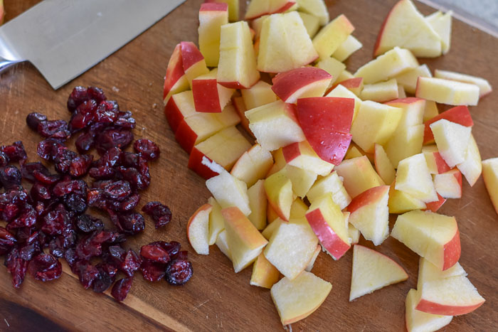 dried cranberries and chopped apple on cutting board