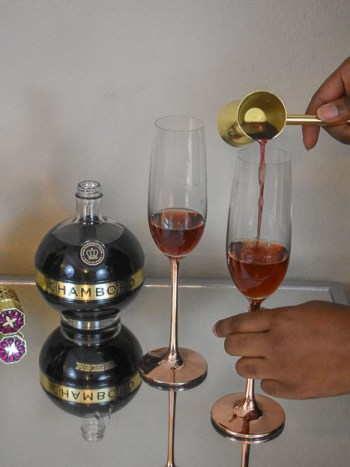 pouring Chambord raspberry liqueur into champagne flutes
