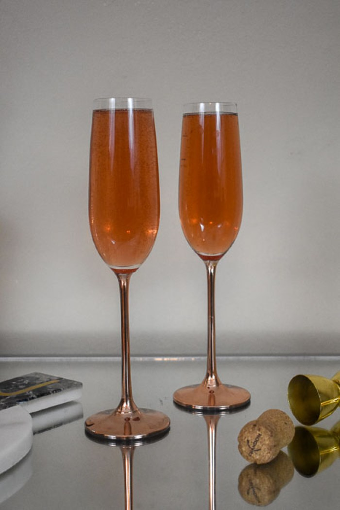 pair of champagne flutes filled with whiskey champagne cocktail