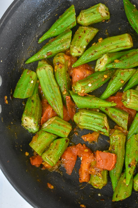 okra, tomato, and crushed red pepper in pan