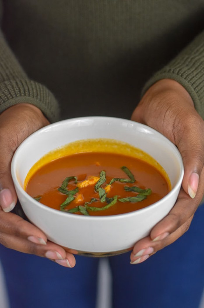 holding bowl of tomato basil chicken soup