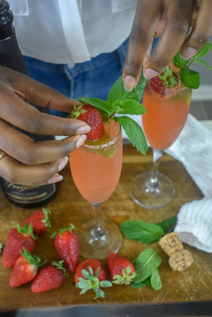 garnishing strawberry mint mimosa with fresh strawberry and sprig of mint leaves.