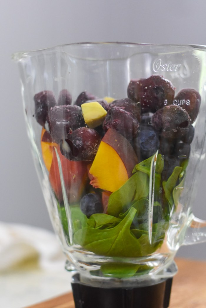 frozen cherries, ginger, peach, blueberries, and spinach leaves in blender