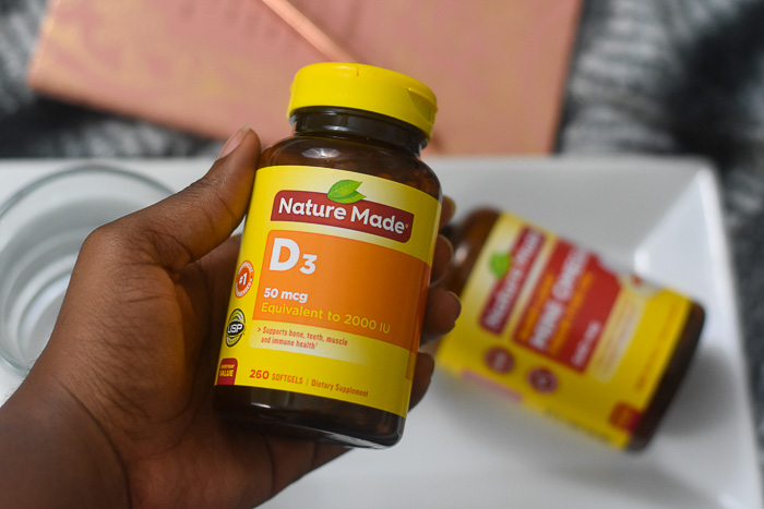 holding bottle of nature made vitamin D