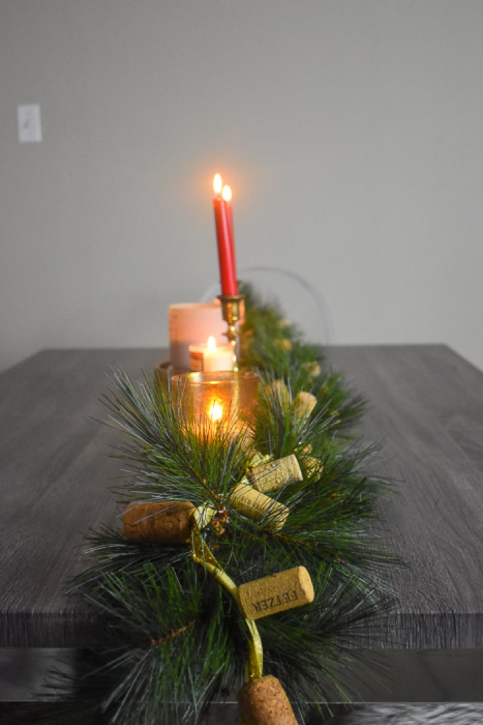 faux pine garland and candles on dining table