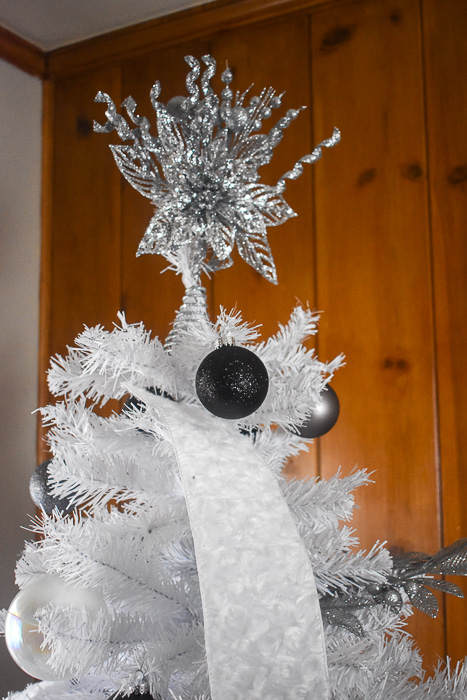 silver glitter Christmas tree topper on white tree