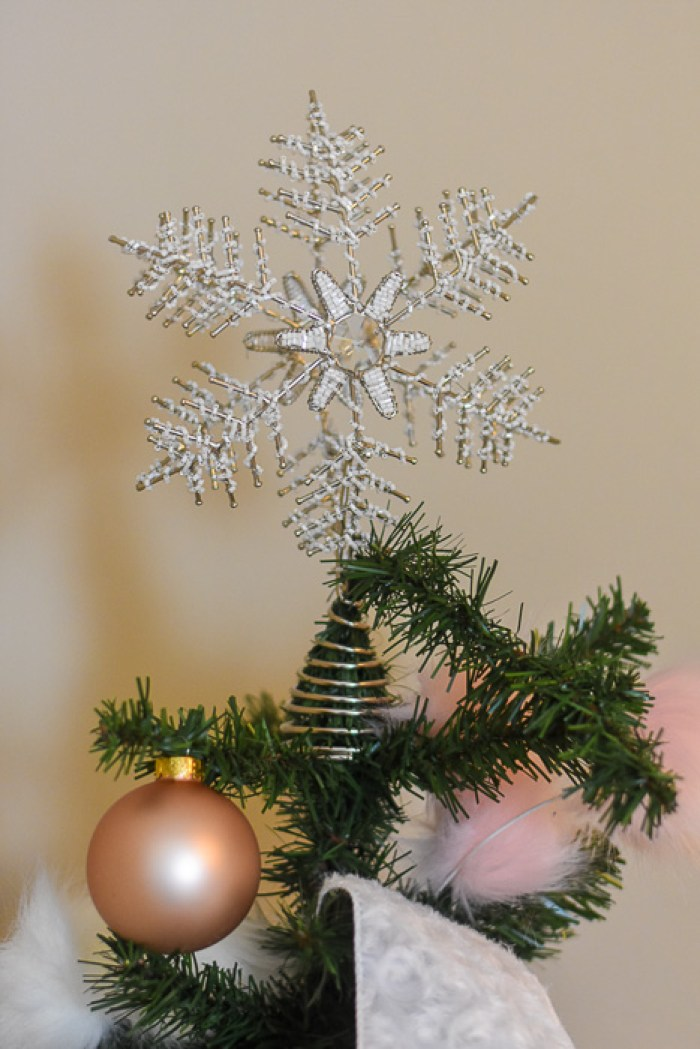 white metal snowflake tree topper on Christmas tree