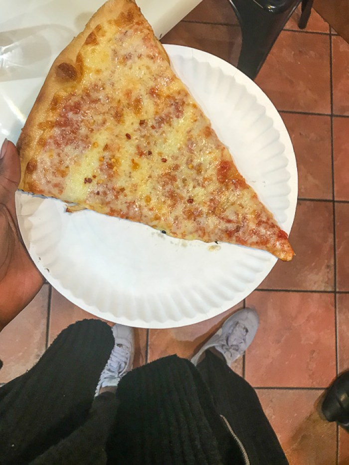 holding NYC cheese pizza slice