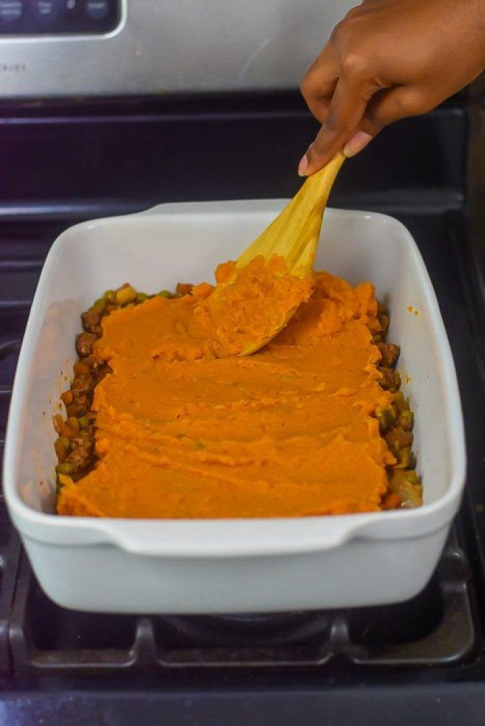 spreading sweet potato topping onto shepherd's pie