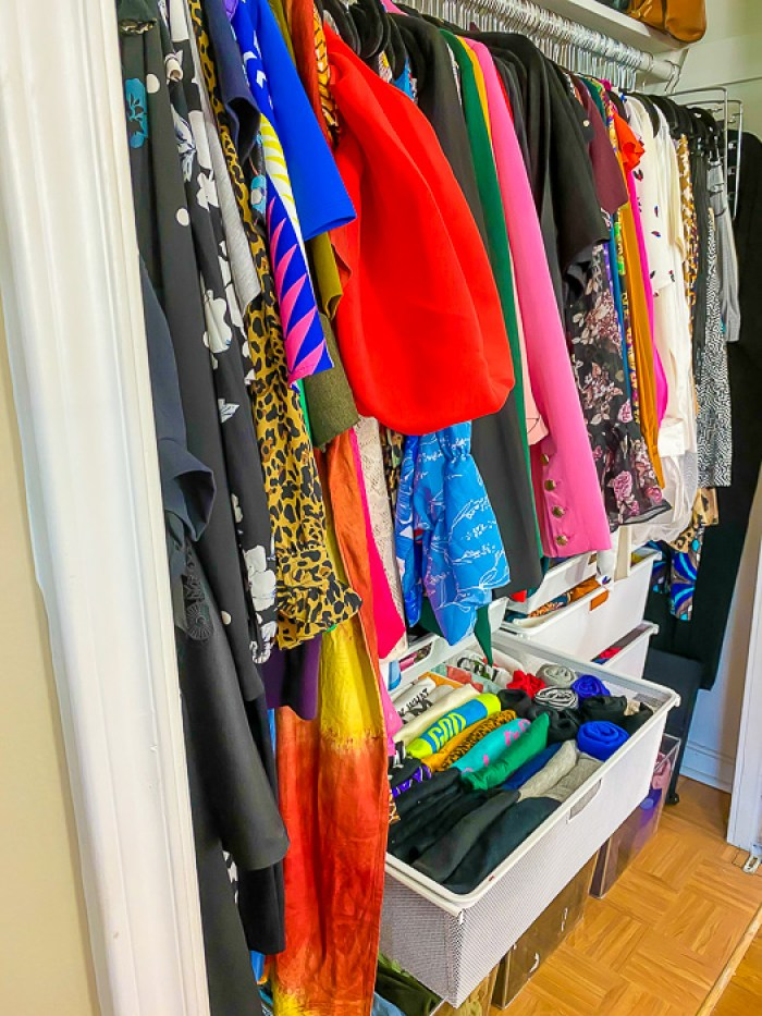 organized clothing closet with hung items and items folded in hanging drawers
