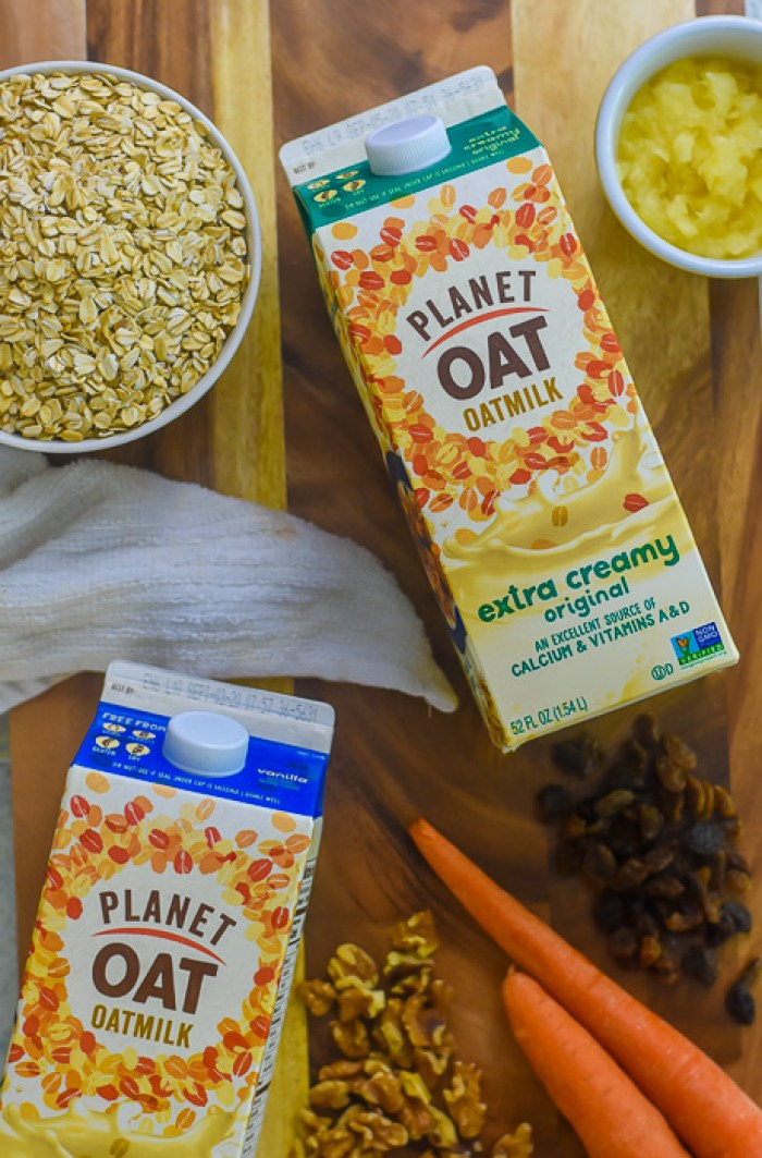 cartons of oat milk and oatmeal breakfast muffin ingredients on cutting board